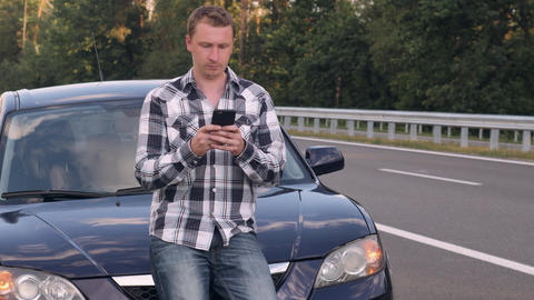 Guy after car accident on the driveway messaging on mobile Footage