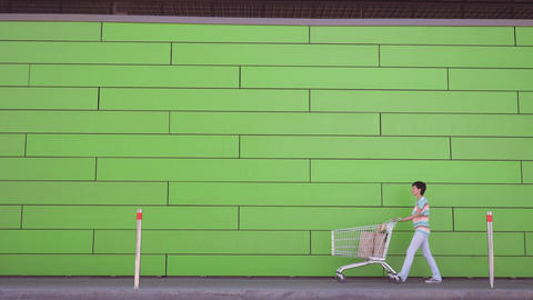Lady walking along green wall with foodstuffs Live Action
