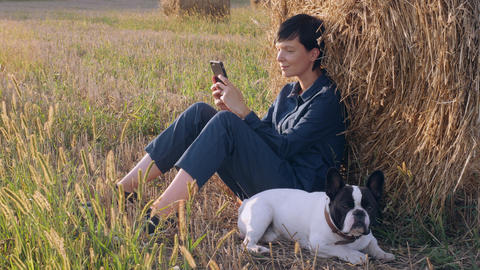 girl with dog resting messaging on smartphone outdoors Footage