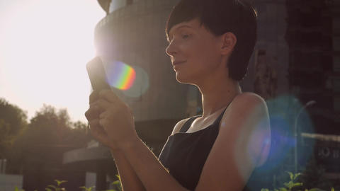 Portrait girl with smartphone outdoors GIF