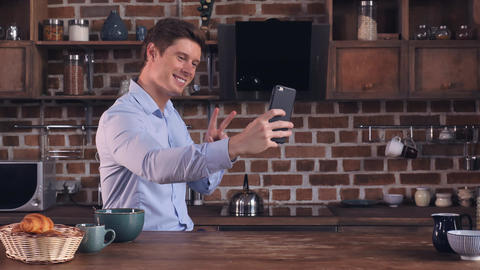 Handsome male using mobile phone in kitchen Footage