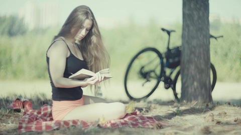 4K Young Attractive Woman Reading Book By The Tree In Park Footage
