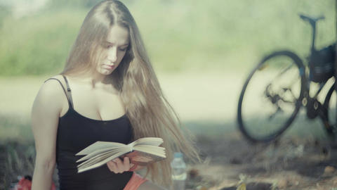 4K Young Attractive Woman Reading A Book In The Park Footage