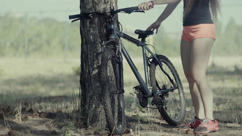 4K The Bicycle Stands Near The Tree. Girl Driving A Bicycle Out Footage