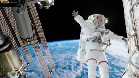 Astronaut working on space station above the Earth. Astronaut Spacewalk, waving Footage