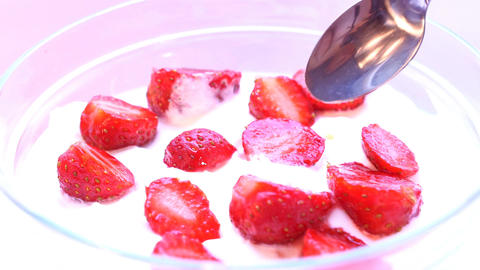 Piece of strawberry is taken from cream by spoon. Macro shot Footage