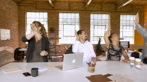 Diverse group of creative business team members celebrating with high fives at a Live Action