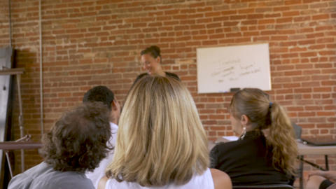 Coworkers smiling and attending a employee meeting on teamwork with a presenter Footage