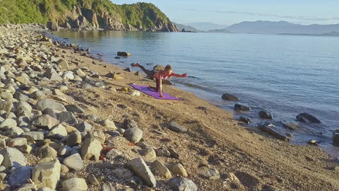 Girl Balances in Yoga Pose against Ocean Lapping Waves Footage