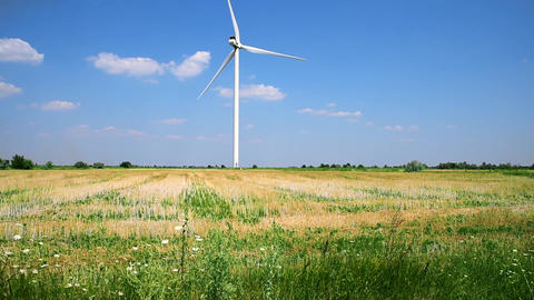 One windmill in a field against a sky with clouds Image