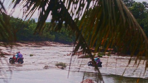 Tourists Ford Flooded River by All Terrain Vehicles in Jungle Live Action