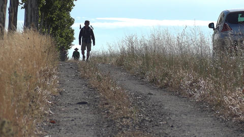 Pilgrim carrying a backpack in the back, going on a country road paved bordered  Footage