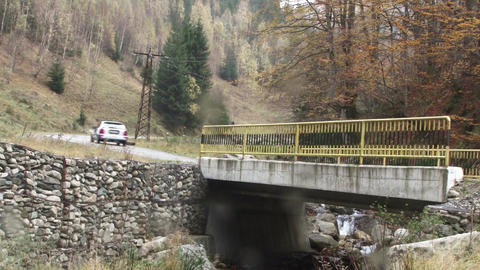 Rally car goes over a bridge. It is filmed on the road after the bridge. Rally t Footage