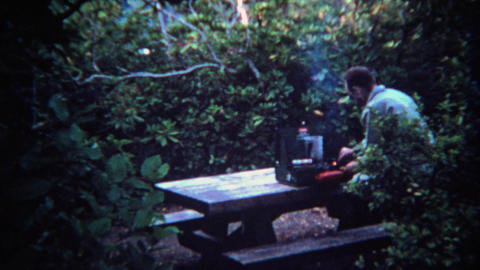 1971: Man lighting camp stove on picnic table in forest wilderness Footage
