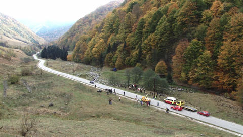 Sequence filmed at a rally on a mountain road in autumn, while 3 cars pass in fr Footage