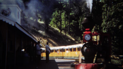 1971: Mini steam powered railroad train ride taking corner Footage