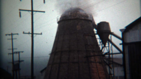 1971: Steam rising from industrial factory lumber mill processing plant Footage