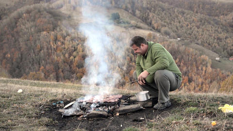Steak and other meat on barbeque grill with flames. A man puts the meat on the h Footage