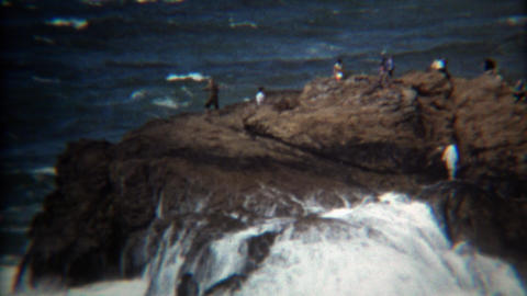 1971: Wave crashes on rocky shoreline almost hitting bystanders Footage