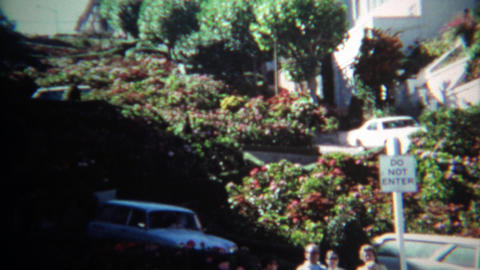 1971: Car turning on curvy famous flower covered Lombard Street Footage