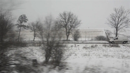 View captured on the window of a train over snowy fields, seen through the trees Footage