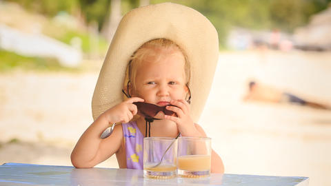 Little Girl in Hat Drinks Juice Takes off Sunglasses Footage