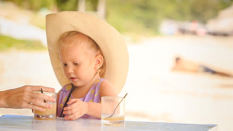 Little Girl in Hat Drinks Juice with Spoon from Glass Footage