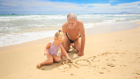 Grandpa Little Blond Girl Sit on Sand Water Washes Drawing out Footage