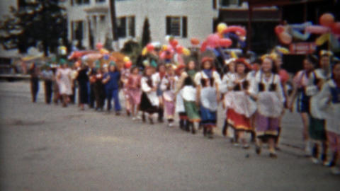 1945: Kids balloon parade walking thru downtown main street Footage