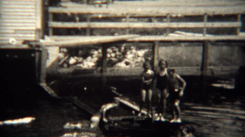 1939: Kids jump into local swimming hole from broken pier Footage