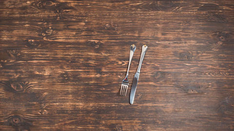 The fork and knife move on a wooden table Footage