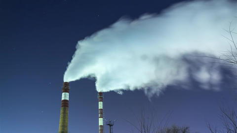Smoking chimneys against the night sky and stars. air pollution and the Footage