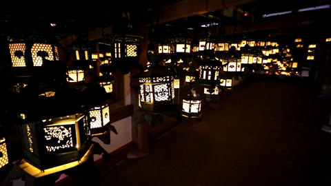 Flickering lanterns hang in a dark room inside Kasuga Taisha, Nara, Japan ビデオ