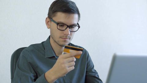 Young man using credit card online Archivo
