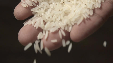 White raw rice grains are falling from a man's hand in slow motion Footage