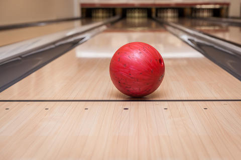red bowling ball on the track in the bowling center Photo