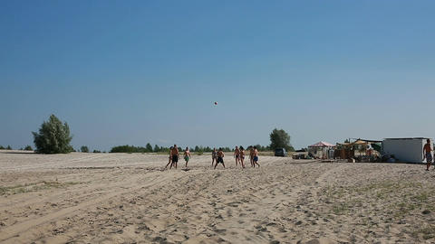 A group of young guys and girls playing beach volleyball ビデオ