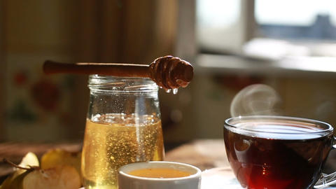 Closeup is authentic honey slowly drains from a spoon. Morning time. Tea Footage
