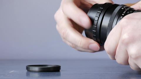 Screwing camera lens filter on a vintage manual focus lens Footage