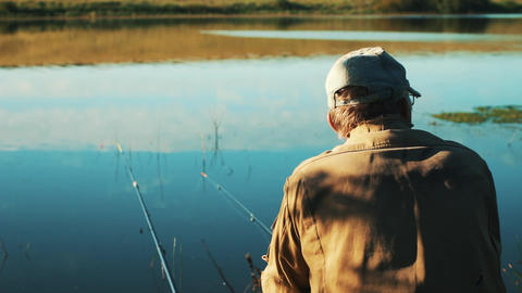 Fisherman with a fishing rod on the shore of the lake. fishing. The fishing rods Live Action