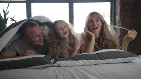 Smiling happy family posing under duvet in bedroom Footage