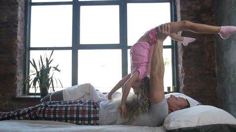 Joyful dad lifting cute curly daughter up in bed ビデオ
