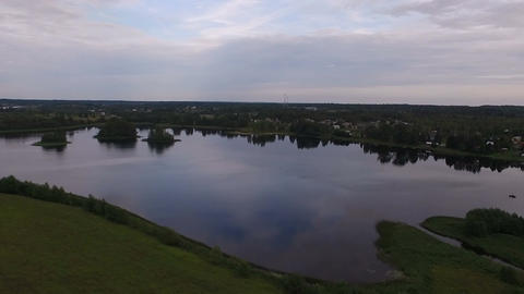 A view from the air to a small calm lake. Summer, green shores, clouds are Filmmaterial