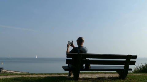 Man enjoying view IJsselmeer and takes pictures with his mobile Live Action