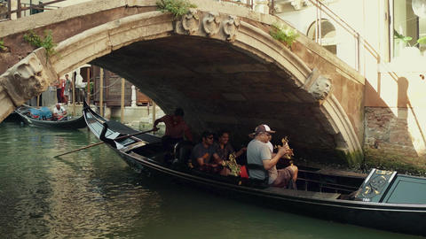 VENICE, ITALY - AUGUST 8, 2017. Venetian gondola with tourists passing under the Footage
