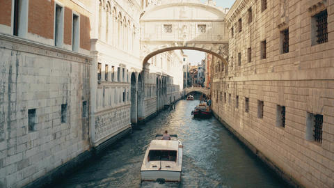Motorboat moving along narrow canal in Venice between old buildings, Italy Footage