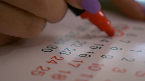 Closeup of woman hand marking dates and days on calendar... Stock Video Footage