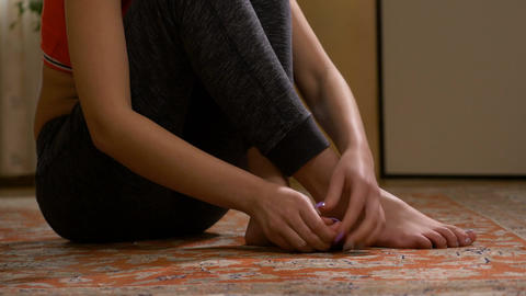 Young lady sitting on floor massaging her toes Footage
