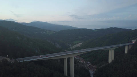 Aerial view of European highway bridge and tunnel in mountains at dusk Footage
