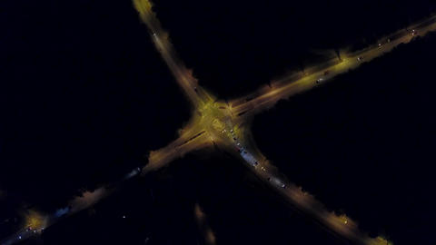 Aerial top down view time lapse of a rural European car road roundabout at night Footage
